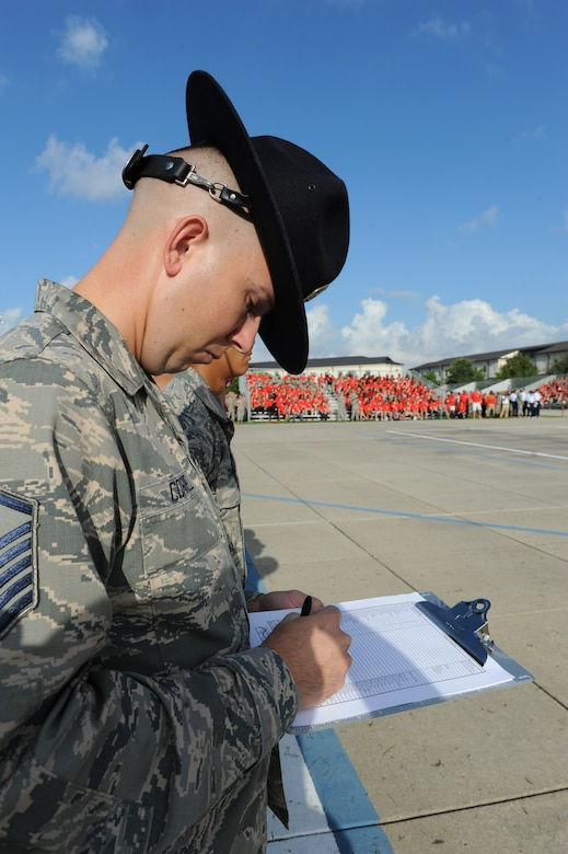 """Master Sgt. James Correll, 2nd Air Force military training instructor, serves as a judge during the 81st Training Group drill down at the Levitow Training Support Facility drill pad Sept. 9, 2016, on Keesler Air Force Base, Miss. The 334th TRS """"Gators"""" placed first in open ranks, regulation and overall. (U.S. Air Force photo by Kemberly Groue/Released)"""