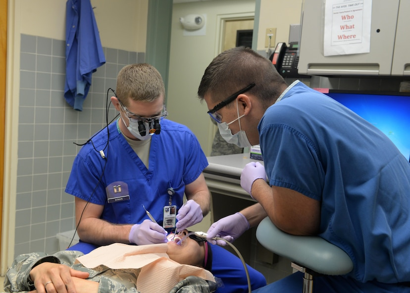 Capt. John Dinan (left), 9th Medical Group general dentist, performs dental work with Senior Airman Noah Jackson, prophy technician March 4, 2016, at Beale Air Force Base, California. The Beale Medical Group will be extending their clinic hours starting Oct. 1, 2016. The changes will expand access to healthcare and allow greater flexibility in scheduling visits. (U.S. Air Force photo/Senior Airman Ramon Adelan)