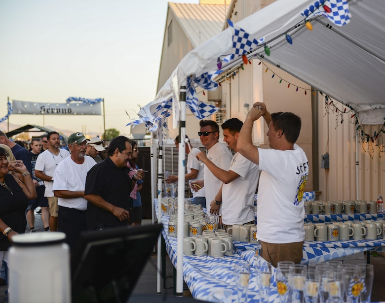 Oktoberfest staff sell beer steins and glasses to attendees at the fest's main entrance during the 20th annual Oktoberfest at Holloman Air Force Base, N.M. on Sept. 10, 2016. Attendees of this year's Oktoberfest enjoyed traditional Bavarian foods, beer and fun activities. (U.S. Air Force photo by Airman Alexis P. Docherty)