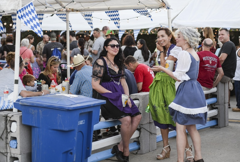 A group of women, wearing traditional dirndl dresses, take a break near a food stand at the 20th annual Oktoberfest at Holloman Air Force Base, N.M. on Sept. 10, 2016. Traditional dirndl dresses are feminine costume dresses and are worn by women during Germany's annual Oktoberfest. (U.S. Air Force photo by Airman Alexis P. Docherty)