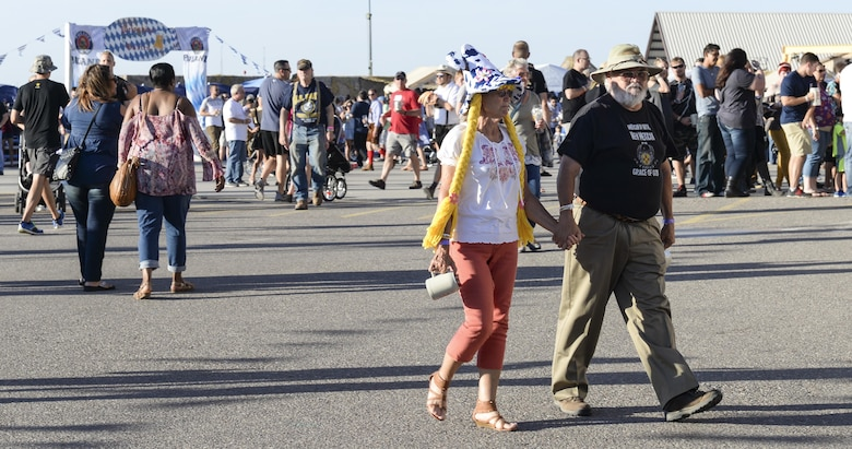 A couple take a stroll and enjoy the sites during the 20th annual Oktoberfest at Holloman Air Force Base, N.M. on Sept. 10, 2016. Thousands of Holloman Airmen and their families attended this year's Oktoberfest. (U.S. Air Force photo by Airman Alexis P. Docherty)