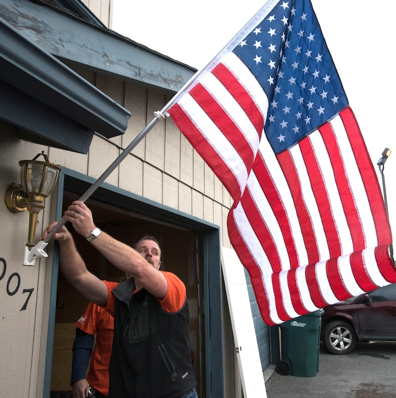 ANCHORAGE, Alaska -- A Hope Depot volunteer affixes an American flag to the residence of Staff Sgt. Sequoya Joseph, a personnelist with the Alaska Air National Guard's 176th Force Support Flight, here Sept. 14, 2016. About 50 volunteers came together to renovate Joseph's home. The effort was the result of a partnership between Home Depot's annual Celebration of Service Campaign and the non-profit That Others May Live Foundation. National Guard photo by Maj. John Callahan.