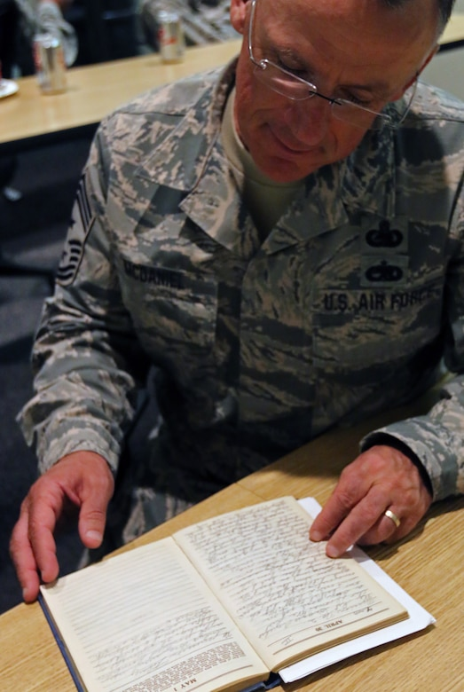 173rd Fighter Wing Command Chief Master Sgt. Mark McDaniel looks at Lt. David R. Kingsley's handwritten journal from WWII, Aug. 31, 2016. WWII veteran Joe Rollison, who married into the Kingsley family and survives his wife of 56 years, donated the historic item to the base during his visit. (U.S. Air National Guard photo by Tech. Sgt. Jefferson Thompson)