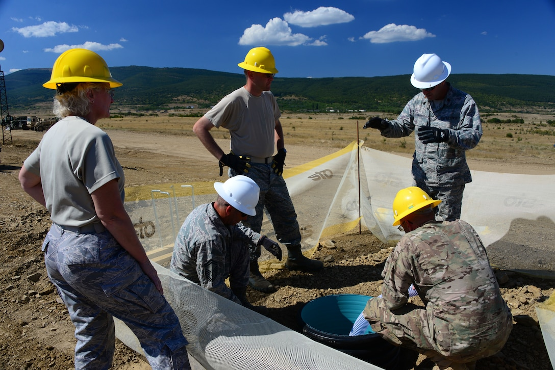Airmen from the 118th Mission Support Group, Tennessee Air National Guard, and the 194th Engineer Brigade, Tennessee Army National Guard, install lighting foundations at the Ammo Holding Area, better known as the AHA, Aug. 16, 2016, at Novo Selo Training Area, Bulgaria.  Tennessee National Guard Soldiers and Airmen were on rotations to complete thier portions of projects as part of Operation Resolute Castle 16, an ongoing operation of military construction to build up Eastern European base infrastructure and help strengthen ties between Tennessee's state partnership with Bulgaria. (U.S. Air National Guard photo by Master Sgt. Kendra M. Owenby, 134 ARW Public Affairs)