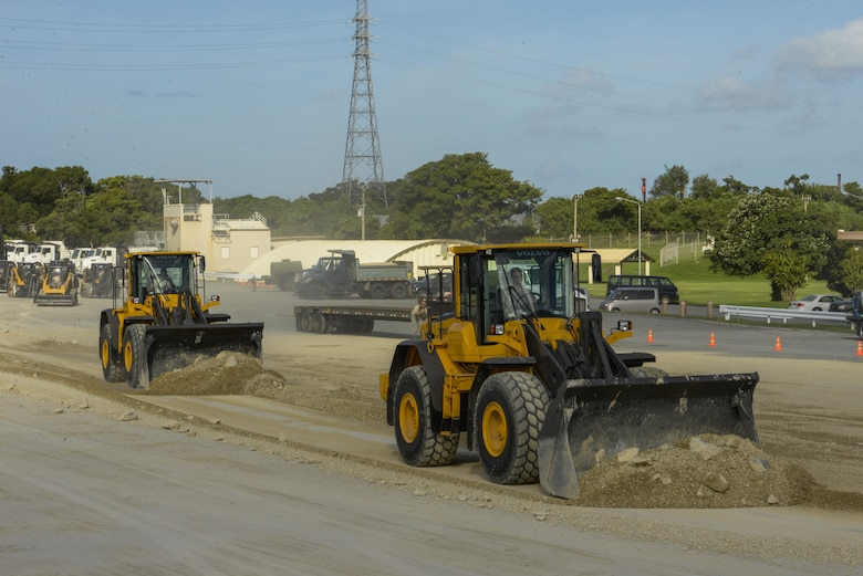 U.S. Air Force Airmen operate heavy machinery to clear debris away from a simulated damaged area created during rapid airfield damage repair training Sept, 15, 2016, at Kadena Air Base, Japan. U.S. Air Force Civil Engineer Squadrons from Kadena, Yakota and Misawa Air Bases teamed up with the Air Force Civil Engineer Center from Tyndall Air Force Base, Fla., to conduct training for the new rapid airfield damage repair (RADR) technique Sept. 12-15. (U.S. Air Force photo by Senior Airman Stephen G. Eigel)