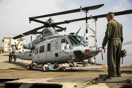 U.S. Marines with Marine Light Attack Helicopter Squadron (HMLA) 469, unload a UH-1Y Venom at Marine Corps Air Station Iwakuni, Japan, Sept. 16, 2016. Three UH-1Y Venoms, two MV-22C Ospreys and one CH-53E Super Stallion, and are scheduled to fly to their destination in Okinawa after concluding preparations at MCAS Iwakuni. The Green Cove, a vehicle carrier, transported the aircraft approximately 6,000 miles from Naval Air Station North Island, San Diego, Calif. Delivering aircraft by boat is more cost effective than flying from the U.S. to Japan, and MCAS Iwakuni has both airport and seaport capabilities, which no other Marine Corps installation has. (U.S. Marine Corps photo by Lance Cpl. Aaron Henson)