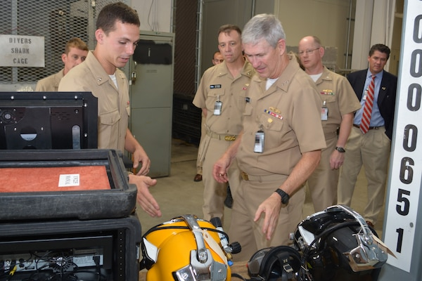 Navy Diver 3rd Class Mitchell Lafave explains the different gear used by the Dive Locker with Naval Sea Systems Command Commander Vice. Adm. Tom Moore as Rear Adm. James Downey, Commander Regional Maintenance Center observes at Southeast Regional Maintenance Center (SERMC) at Jacksonville, Fla. Sept. 1st. Photo by Scott Curtis.
