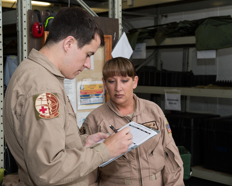 Staff Sgt. Jarrett Lyle, 10th Expeditionary Aeromedical Evacuation Flight technician, and Senior Master Sgt. Theresa Sheheen, 10th EAEF superintendent, review a checklist at Ramstein Air Base, Germany, Sept. 9, 2016. Before departing on a mission, Airmen from the 10th EAEF must read through multiple checklists to ensure supplies, equipment, and safety are accounted for. (U.S. Air Force photo/Senior Airman Jimmie D. Pike)