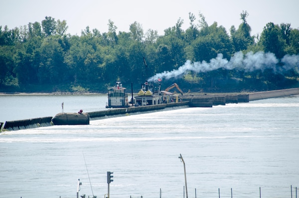 The steam work boat lifts the smaller wickets near the bear trap section of the dam to retain pool depth for navigation at Locks and Dam 52 on the Ohio River at Brookport, Illinois.
