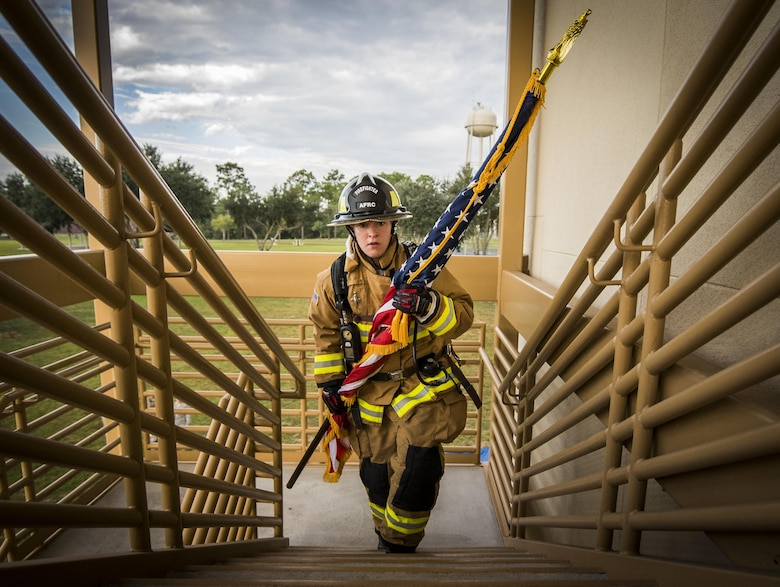 Airman Virginia Davis, from the 919th Special Operations Civil Engineer Squadron, carries an American flag up a flight of stairs while wearing her firefighter gear during a 9/11 memorial stair climb event at Duke Field, Fla., Sept. 11, 2016. The 24-hour climb began at 8:46 a.m. with the 919th Special Operations Wing commander walking the flag up the outside stairwell of the base's billeting facility. Wing Airmen took turns walking the flag up and down the stairwell the entire day until it was delivered to a firefighter and security forces color guard at 8:46 a.m. the next morning for a 9/11 remembrance ceremony. More than 115 Airmen carried the flag throughout the day and night for a total of more than 207,000 steps. (U.S. Air Force photo/Tech. Sgt. Sam King)