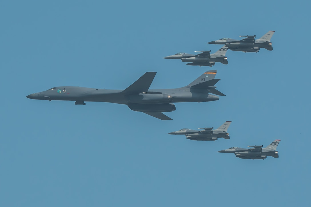 A U.S. Air Force B-1B Lancer, escorted by U.S. Air Force F-16 Fighting Falcons, performs a flyover over Osan Air Base, ROK, Sept. 13, 2016. The flyover highlighted the close cooperation between American and ROK military forces that keeps them ready to respond at any time to threats to stability and security. The B-1s are currently assigned to Andersen Air Force Base, Guam. (U.S. Air Force photo by Senior Airman Dillian Bamman)