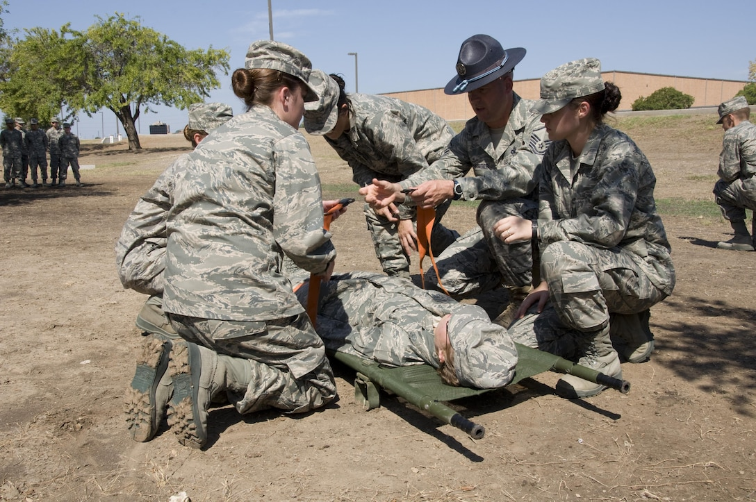 3rd WOT Trainees securing simulated wounded patient to litter during self-aid and buddy care class.