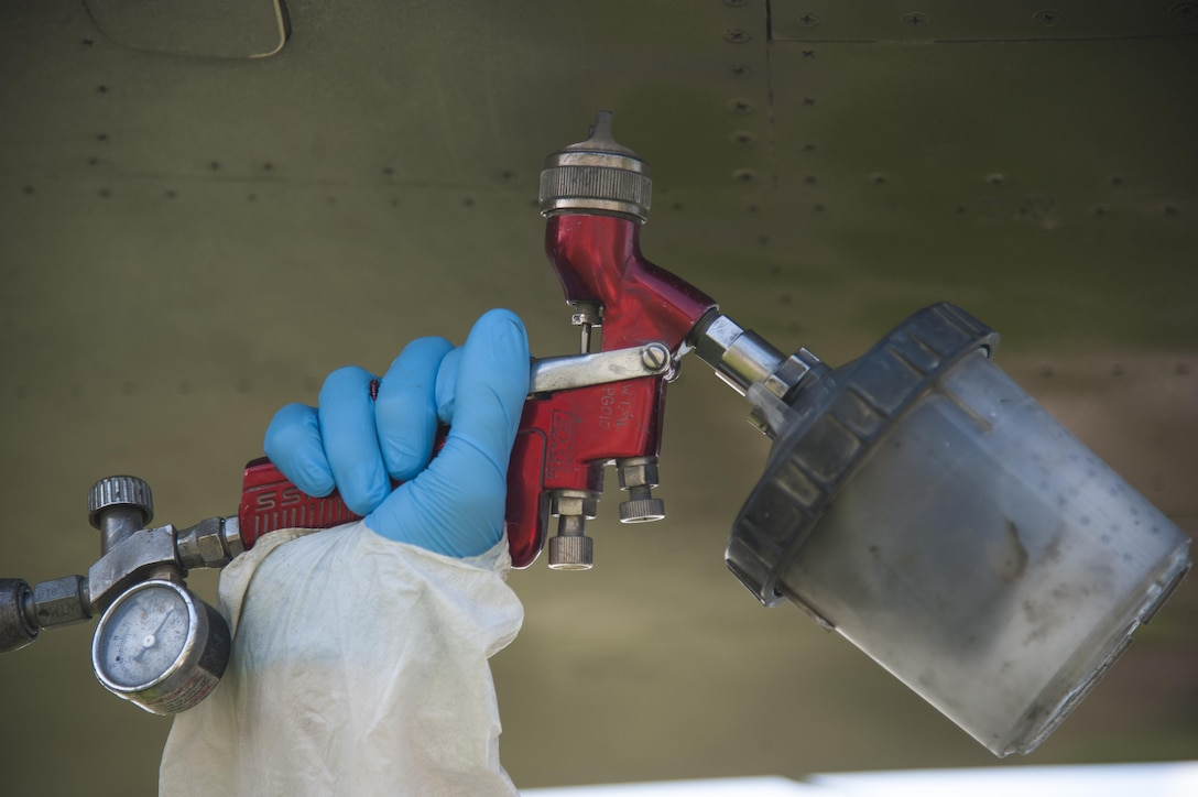 """A low observable technician from the 509th Maintenance Squadron sprays a coating of paint on an FB-111A General Dynamics Aardvark static display at Whiteman Air Force Base, Mo., Sept. 13, 2016. After previously being painted solid gray, the aircraft will now have a """"dark vark"""" scheme of dark green and gray. (U.S. Air Force photo by Senior Airman Joel Pfiester)"""