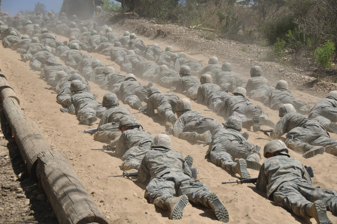 6th WOT Trainees use the low crawl tactical movement under hostile fire during the Tactical Drill Mission at BEAST.