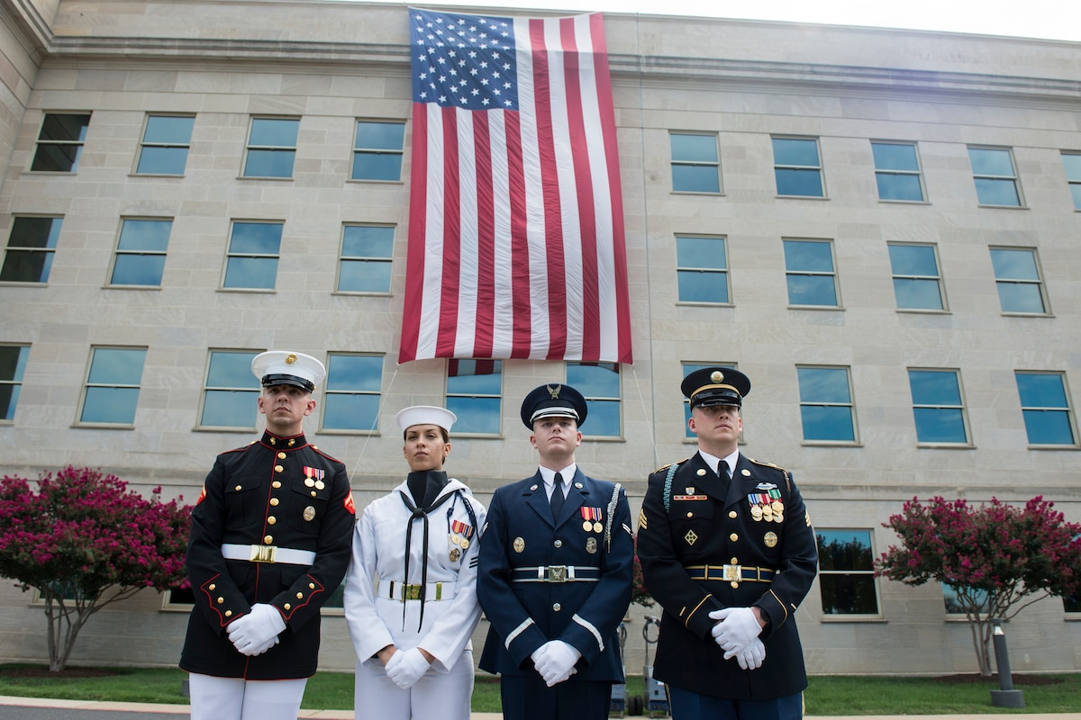 Service members stand before the American flag draping the Pentagon.