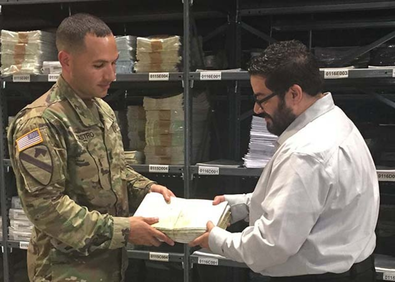 Flight Information Publications Program Manager Julio Bultron, right, hands off an aeronautical map that was printed on demand to Army Captain Joel Castro from the 3-82 General Support Aviation Battalion, 82nd Combat Aviation Brigade, 82nd Airborne Division, Sept. 14, 2016.  Bultron is helping to staff the new Geospatial Intelligence - Forward Presence Team on Fort Bragg, North Carolina.  Defense Logistics Agency Aviation Customer Operations Directorate's Mapping Division will host a facility open house Sept. 28 from 10 a.m. to 2 p.m. at the U.S. Army Forces Command Intelligence Readiness and Operations Center on Fort Bragg, North Carolina.
