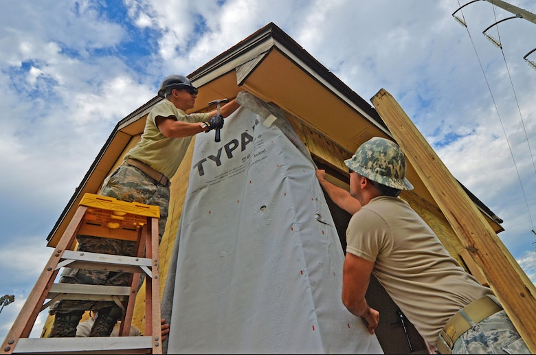 Staff Sgt. Michael Kitzler and Tech. Sgt. Nate Dowling, structural specialists with the 556th RED HORSE, secure house wrap around the softball field press box at Hurlburt Field Fla., Sept. 12, 2016. House wrap is used as insulation to keep moisture out of an infrastructure. (U.S. Air Force photo by Senior Airman Andrea Posey)