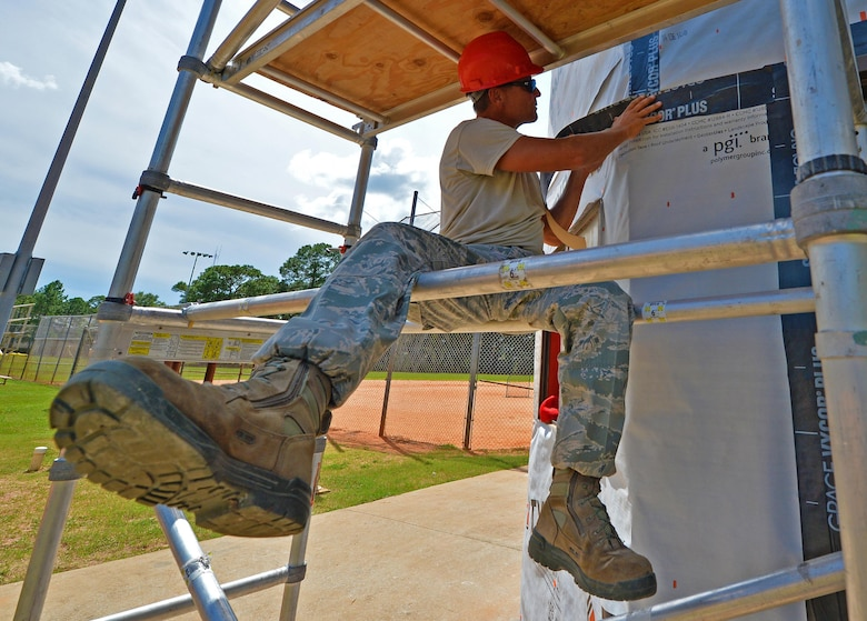 Master Sgt. David Feerick, a structural superintendent with the 556th RED HORSE, presses a roofing underlayment on the wall of the softball field press box at Hurlburt Field Fla., Sept. 13, 2016. This underlayment seals cracks and openings to prevent moisture and other hazards from entering a building. (U.S. Air Force photo by Senior Airman Andrea Posey)