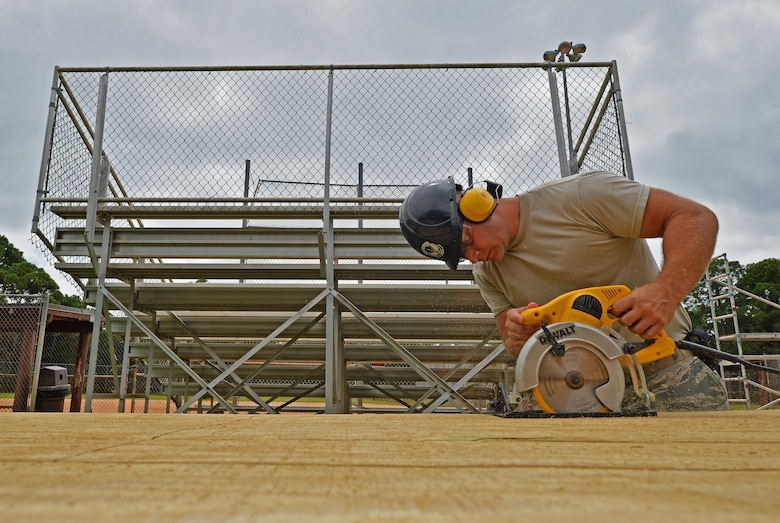 Tech. Sgt. Rickey Schaefer, a structural journeyman with the 556th RED HORSE, cuts planks of wood with a buzz saw during the renovation of the softball field press box at Hurlburt Field Fla., Sept. 14, 2016. These planks are used as exterior walls for the softball field press box. (U.S. Air Force photo by Senior Airman Andrea Posey)