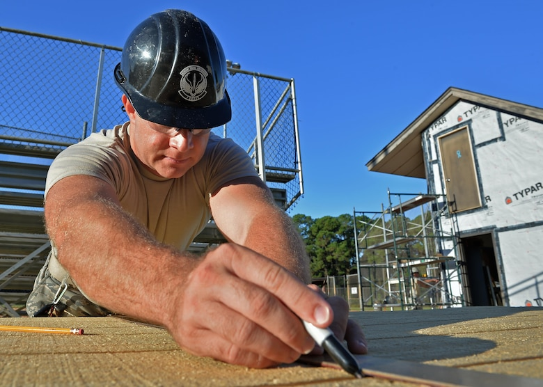 Tech. Sgt. Rickey Schaefer, a structural journeyman with the 556th RED HORSE, marks a plank of wood before cutting it during the renovation of the softball field press box at Hurlburt Field Fla., Sept. 15, 2016. Structural specialists are responsible for constructing and repairing structures on base. (U.S. Air Force photo by Senior Airman Andrea Posey)