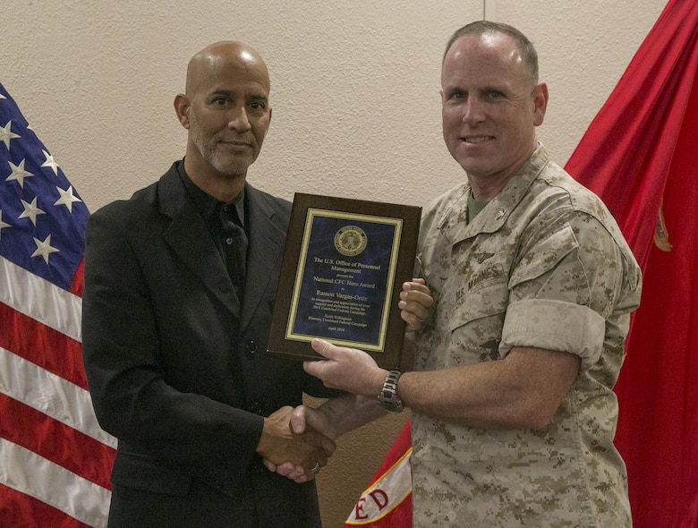 Col. James Harp, Combat Center Chief of Staff, presents the Combined Federal Campaign Hero Award to Ramon Victor-Ortiz, adjutant, G-1 Manpower, during the Combined Federal Campaign Kick-off luncheon at the Frontline Restaurant, Sept. 9, 2016. (Official Marine Corps photo by Lance Cpl. Dave Flores/Released)