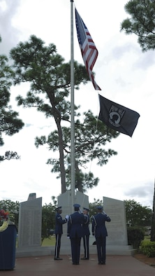 Members of the Hurlburt Field Honor Guard raise the POW-MIA flag during a ceremony at Hurlburt Field, Fla., Sept. 16, 2016. A POW-MIA ceremony marked the end of a 24-hour ruck-march vigil in remembrance of prisoners of war and those identified as missing in action. (U.S. Air Force photo by Airman Dennis Spain)