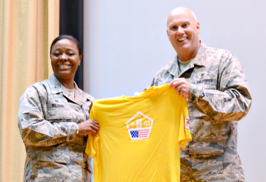 Chaplain (Maj.) Paul Joyner presented 72nd Air Base Wing Commander Col. Stephanie Wilson with a personalized shirt for the 9-11 Memorial Run during the 9-11 Resiliency Luncheon Sept. 8. The luncheon also featured Staff Sgt. Larry Coffie, with the 552nd Aircraft Maintenance Squadron, reading his winning Freedom Citation essay, as well as Chaplain Joyner speaking about the significance of the theme of this year's 9-11 memorial events, United, Remember, Defend. (Air Force photo by Kelly White)