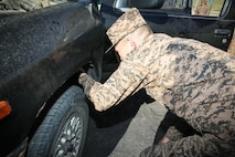 A Mongolian Armed Forces service member inspects a vehicle at a vehicle control point during Non-Lethal Weapons Executive Seminar (NOLES) 2016 at the Five Hills Training Area, Mongolia, Sept. 13, 2016. U.S. Marines with 3rd Law Enforcement Battalion, III Marine Expeditionary Force, instruct the Mongolian Armed Forces about the importance of vehicle control points training while maintaining peacekeeping operations. NOLES is a regularly scheduled field training exercise and leadership seminar hosted annually by various nations throughout Asia-Pacific.