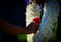 A Rancho High School Junior ROTC cadet places a red rose in a white wreath at the Prisoner of War/Missing in Action Ceremony at Freedom Park on Nellis Air Force Base, Nev., Sept. 16, 2016. Cadets placed a red rose on the white wreath for the Nevada deceased prisoners of war or military members missing in action to represent respect for those individuals. (U.S. Air Force photo by Airman 1st Class Nathan Byrnes)