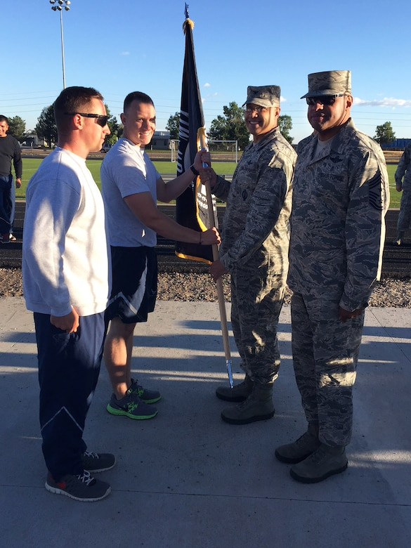 U.S. Air Force Col. David Miller Jr., 460th Space Wing commander, passes the POW/MIA flag to -–Staff Sgt. Jacob Frierdich, 460th Security Forces Squadron unit deployment manager to kick off a 24-hour memorial run Sept. 15, 2016, at an outdoor track on Buckley Air Force Base, Colo. The run served as remembrance of those servicemen and women who never returned home. (U.S. Air Force photo by Airman 1st Class Gabrielle Spradling/Released)