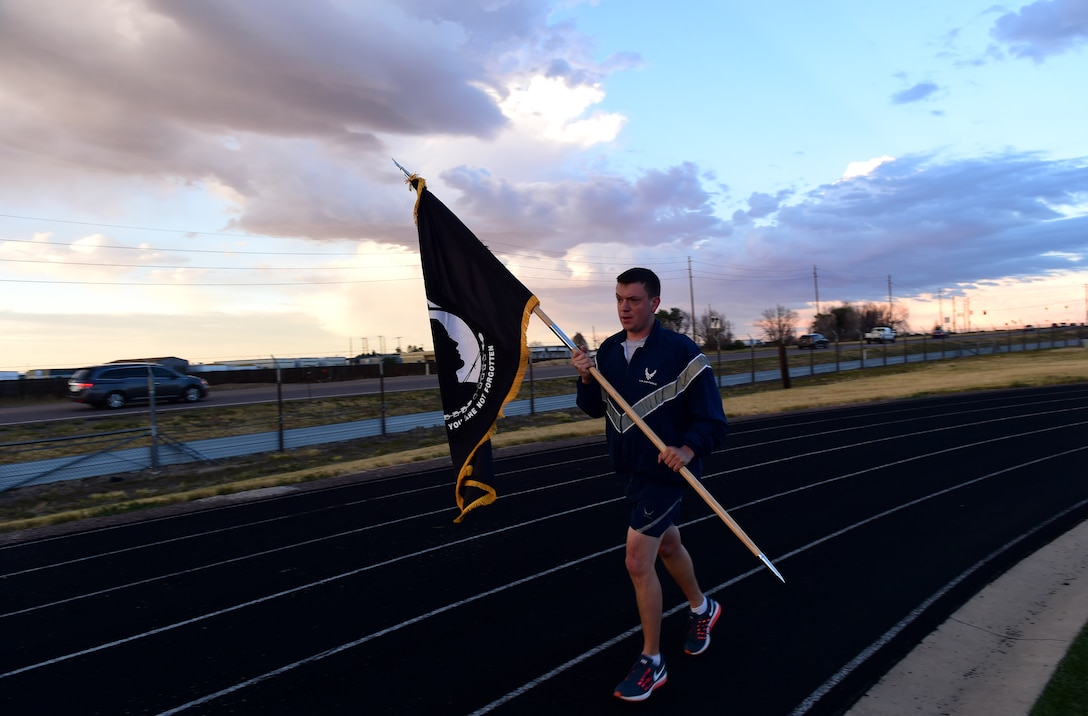 A participant in a 24-hour POW/MIA memorial run  carries a flag Sept. 15, 2016, at an outdoor track on Buckley Air Force Base, Colo. Team Buckley members ran in two-hour shifts to remember those service members who sacrificed their lives. (U.S. Air Force photo by Airman 1st Class Gabrielle Spradling/Released)