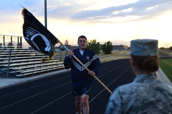 Team Buckley members prepare to pass the POW/MIA flag during a 24-hour memorial run Sept. 15, 2016, at an outdoor track on Buckley Air Force Base, Colo. The flag reminds all who see it the service members imprisoned or missing in action are not forgotten.. (U.S. Air Force photo by Airman 1st Class Gabrielle Spradling/Released)