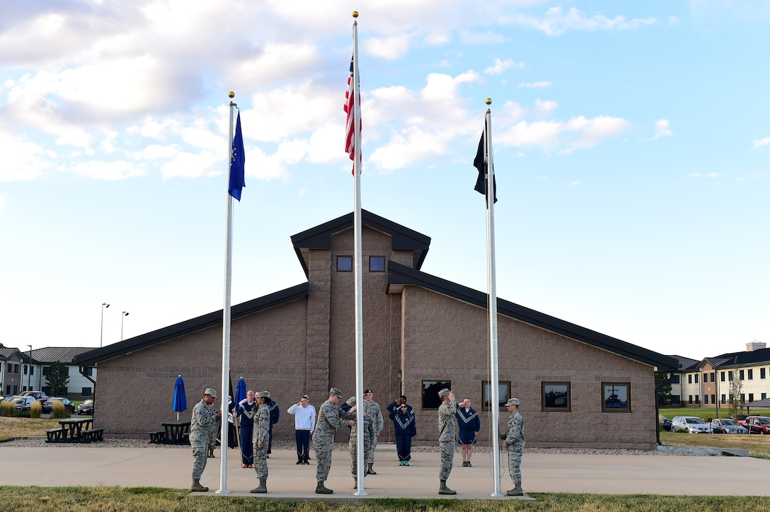 Team Buckley Airman Leadership School students salute as the flags are raised during a 24-hour POW/MIA memorial run Sept. 16, 2016, at an outdoor track on Buckley Air Force Base, Colo.  The run served as remembrance of those servicemen and women who never returned home. (U.S. Air Force photo by Airman 1st Class Gabrielle Spradling/Released)