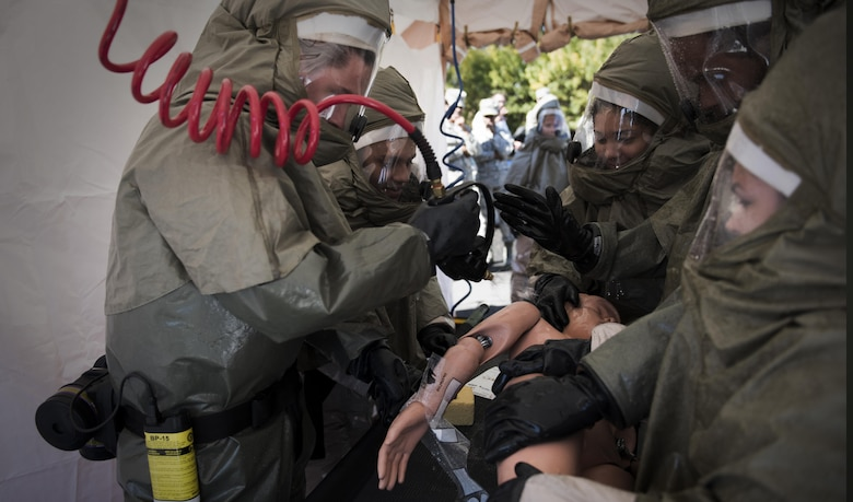 Fairchild Airmen conduct a non-ambulatory patient decontamination during a mock decontamination training exercise Sept. 16, 2016, at Fairchild Air Force Base, Wash. The biannual training is broken up into six hours of lectures, two hours of personal-protective equipment training, a one hour written exam, six hours of hands-on equipment training and one hour of equipment cleaning. (U.S. Air Force photo/Airman 1st Class Sean Campbell)