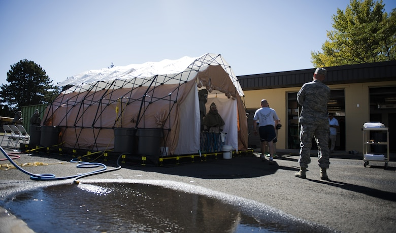 Fairchild Airmen set up a decontamination tent during a mock decontamination training exercise Sept. 16, 2016, at Fairchild Air Force Base, Wash. The hands-on portion of the training is a full test of mission capability, which includes setting up the decontamination tent and having team members put on their protective suits in less than 15 minutes. (U.S. Air Force photo/Airman 1st Class Sean Campbell)