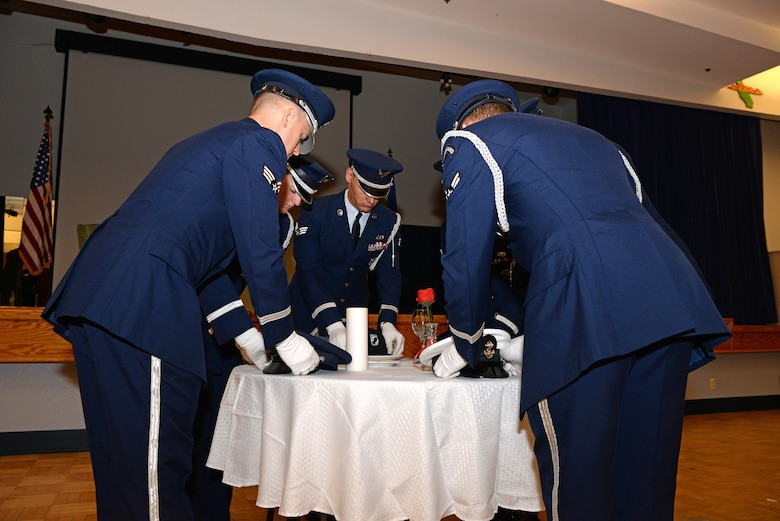 The Beale Air Force Base Honor Guard places the service covers of all the branches of the military on a table to honor the service members who were prisoners of war or those who remain missing in action at the POW/MIA ceremonial breakfast Sept. 15, 2016, at Beale Air Force Base, California. More than 82,000 American service members are still considered missing in action. (U.S. Air Force photo/Airman Tristan D. Viglianco)