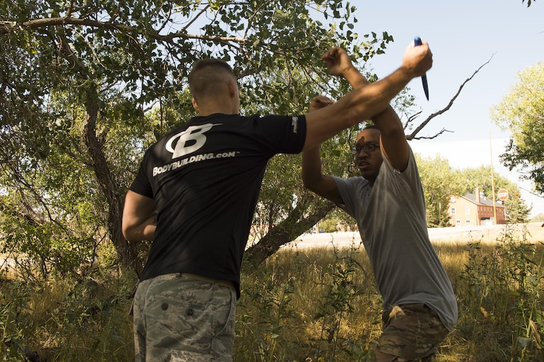 Staff Sgt. Andrew Stokes, 341st Security Forces Squadron NCO in charge of unit scheduling, defends against a prop-knife attack by Tech. Sgt. Aitor Simpson, 91st Missile Security Forces Squadron flight security controller, during a Krav Maga certification course at F.E. Warren Air Force Base, Sept. 14, 2016. Defending against a knife attack was just one of many self-defense maneuvers taught. The 20th Air Force ICBM Center of Excellence offers multiple training and professional development courses throughout the year for all Airmen, regardless of rank or Air Force specialty code. (U.S. Air Force photo by Staff Sgt. Christopher Ruano)