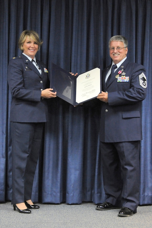 Chief Master Sgt. Derek Williams, chief of Cyber Intelligence operations for the 223rd Intelligence Flight, receives the Certificate of Retirement from Maj. Roxanne Westmoreland, flight commander, during a ceremony held in his honor at the Kentucky Air National Guard base in Louisville, Ky., July 16, 2016. Williams officially retired from the Air Force, Air Force Reserve and Air National Guard after 32 years of service. (U.S. Air National Guard photo by Tech. Sgt. Vicky Spesard)