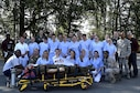 Nursing students from Caritas SchulZentrum St. Hildegard, Saarbrücken, Germany, along with medics from the 86th Aeromedical Evacuation Squadron, and 86th Medical Group simulation team members pose for a photo after a simulated mass casualty training scenario at Ramstein Air Base, Germany, Sept. 13, 2016. The visit allowed the students to learn opportunities where Air Force nurses can incorporate their skillsets and training in an environment outside of the traditional clinical setting. (U.S. Air Force photo by Senior Airman Jonathan Bass)