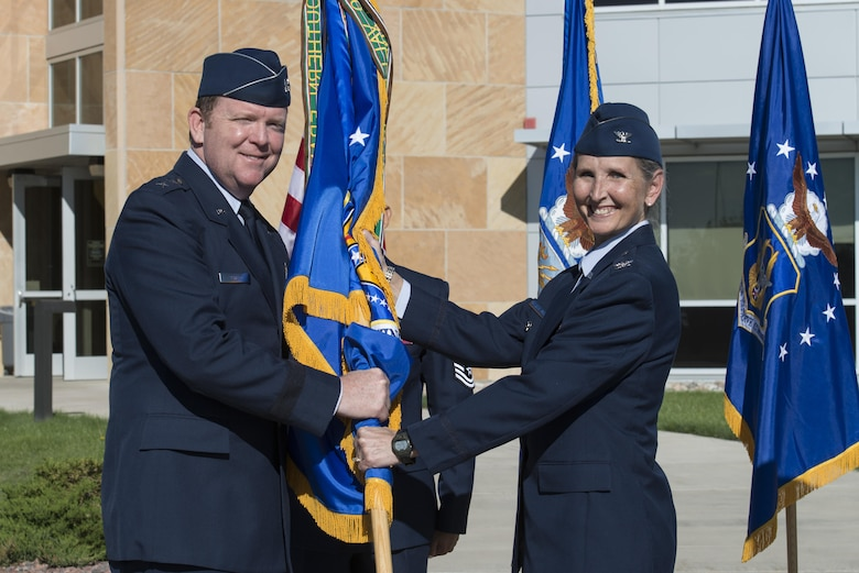 Col. Traci L. Kueker-Murphy receives the 310th Space Wing colors from Maj. Gen. Richard W. Scobee, 10th Air Force commander, during a change of command ceremony as she assumes command of the 310th Space Wing, Schriever AFB, Colo., Sept. 17, 2016. 