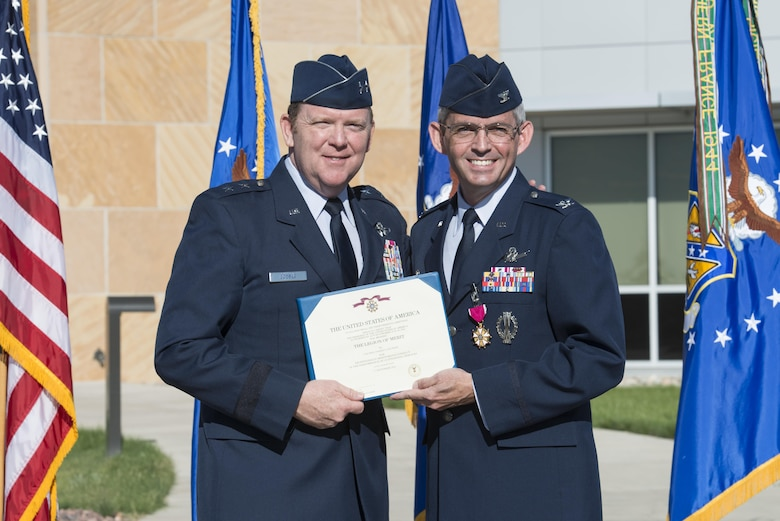 Maj. Gen. Richard W. Scobee, 10th Air Force commander, presents Col. Damon S. Feltman with the Legion of Merit award for his service during the colonel's time as commander of the 310th Space Wing during a change of command ceremony, Schriever AFB, Colo., Sept. 17, 2016.