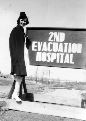 Anne Rissman poses in front of a sign of one of the hospitals she worked at during World War II. She made the journey across the Atlantic Ocean aboard the Queen Mary along with 5,000 other personnel to support the United States during WWII. (Courtesy Photo)