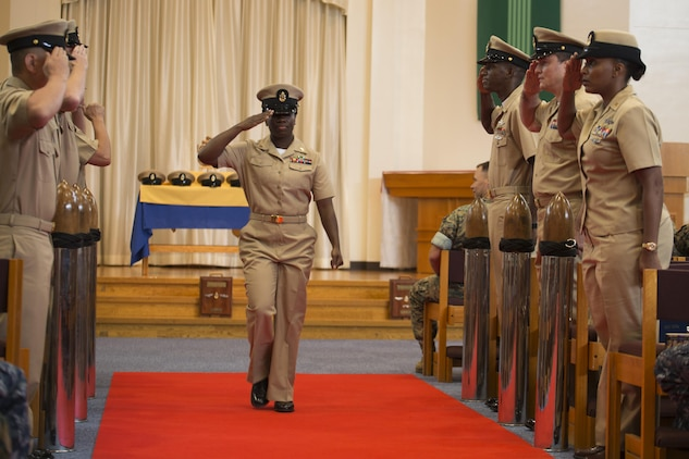 U.S. Navy Chief Petty Officer Lamonica Harrison, chief hospital corpsman with MCAS Iwakuni's base health clinic, salutes her peers as she walks down the red carpet during a promotion ceremony in the Marine Memorial Chapel at Marine Corps Air Station Iwakuni, Japan, Sept. 16, 2016. Harrison said being in front of her peers and receiving the honor of chief petty officer filled her with pride and joy. (U.S. Marine Corps photo by Lance Cpl. Joseph Abrego)