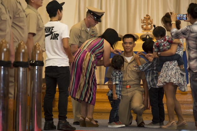 U.S. Navy Chief Petty Officer Johnerikson Angeles, chief aviation machinist mate with Aircraft Intermediate Maintenance Detachment, kneels while being pinned during a promotion ceremony in the Marine Memorial Chapel at Marine Corps Air Station Iwakuni, Japan, Sept. 16, 2016. Angeles chose to be pinned by his wife and kids in appreciation of their support for his service as a Sailor. (U.S. Marine Corps photo by Lance Cpl. Joseph Abrego)