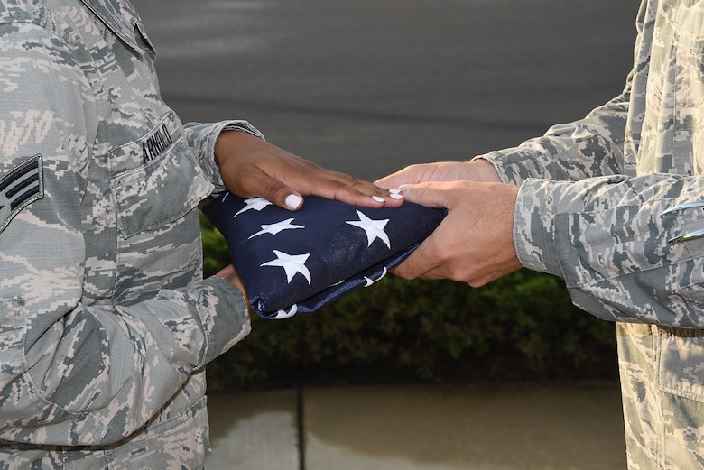 Senior Airman Chelcee Arnold passes the American Flag to Senior Master Matthew Smith at the Retreat ceremony at the 164th Airlift Wing in Memphis, Tenn on August 7, 2016. (U.S. Air National Guard photo by Master Sergeant Danial Mosher/Released)