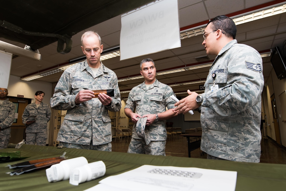 Lt. Gen. (Dr.) Mark A. Ediger, Surgeon General of the Air Force, Headquarters U.S. Air Force, Washington, D.C., and Chief Master Sgt. Jason Pace, Office of the Surgeon General medical enlisted force chief, receive a briefing by Staff Sgt. Johan Rodriguez, 51st Medical Support Squadron logistics technician, on the 51st Medical Group's Biological Warfare/Chemical Warfare program Sept. 14, 2016, at Osan Air Base, Republic of Korea. The BW/CW program is designed to take contingency medical care and import it into squadrons across Osan to better prepare for contingency operations. (U.S. Air Force photo by Senior Airman Dillian Bamman)
