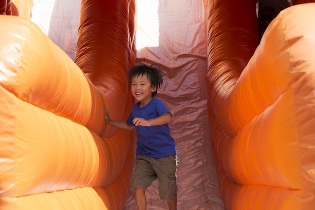 A local child smiles after coming down a slide during the Boys and Girls Club Day for Kids Celebration 2016 at Marine Corps Air Station Iwakuni, Japan, Sept. 17, 2016. The celebration offered bouncy houses, slides and other fun-filled activities for the children who attended. (U.S. Marine Corps photo by Lance Cpl. Joseph Abrego)