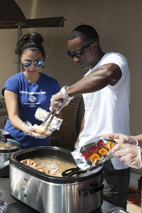 Volunteers prepare hot dogs during the Boys and Girls Club Day for Kids Celebration 2016 at Marine Corps Air Station Iwakuni, Japan, Sept. 17, 2016. The celebration offered snacks for the guests who attended such as hot dogs, cotton candy, popcorn and shaved ice. (U.S. Marine Corps photo by Lance Cpl. Joseph Abrego)