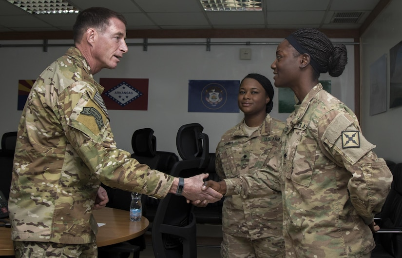 Command Sgt. Maj. William Thetford, left, the senior enlisted leader of U.S. Central Command, presents a coin to Spc. Rena Hildreth, right, a unit supply specialist with the 77th Combat Aviation Brigade on Sep. 15, 2016 at Camp Buehring, Kuwait. Thetford recognized several Soldiers with coins for their military excellence during his two-day visit to Kuwait. (U.S. Army photo by Sgt. Angela Lorden)