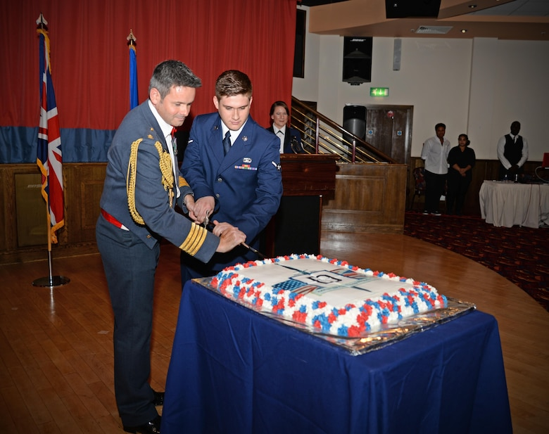 Royal Air Force Group Captain Richard Davies, left, RAF Marham Station Commander, and U.S. Air Force Airman Dylan Aubrey, 100th Force Support Squadron customer service apprentice, cut a cake during the Air Force Ball as part of opening of the ceremony Sept. 17, 2016, on RAF Mildenhall, England. Individuals chosen to cut the cake are traditionally those with the least and the greatest amount of time in service. (U.S. Air Force photo by Senior Airman Christine Halan)